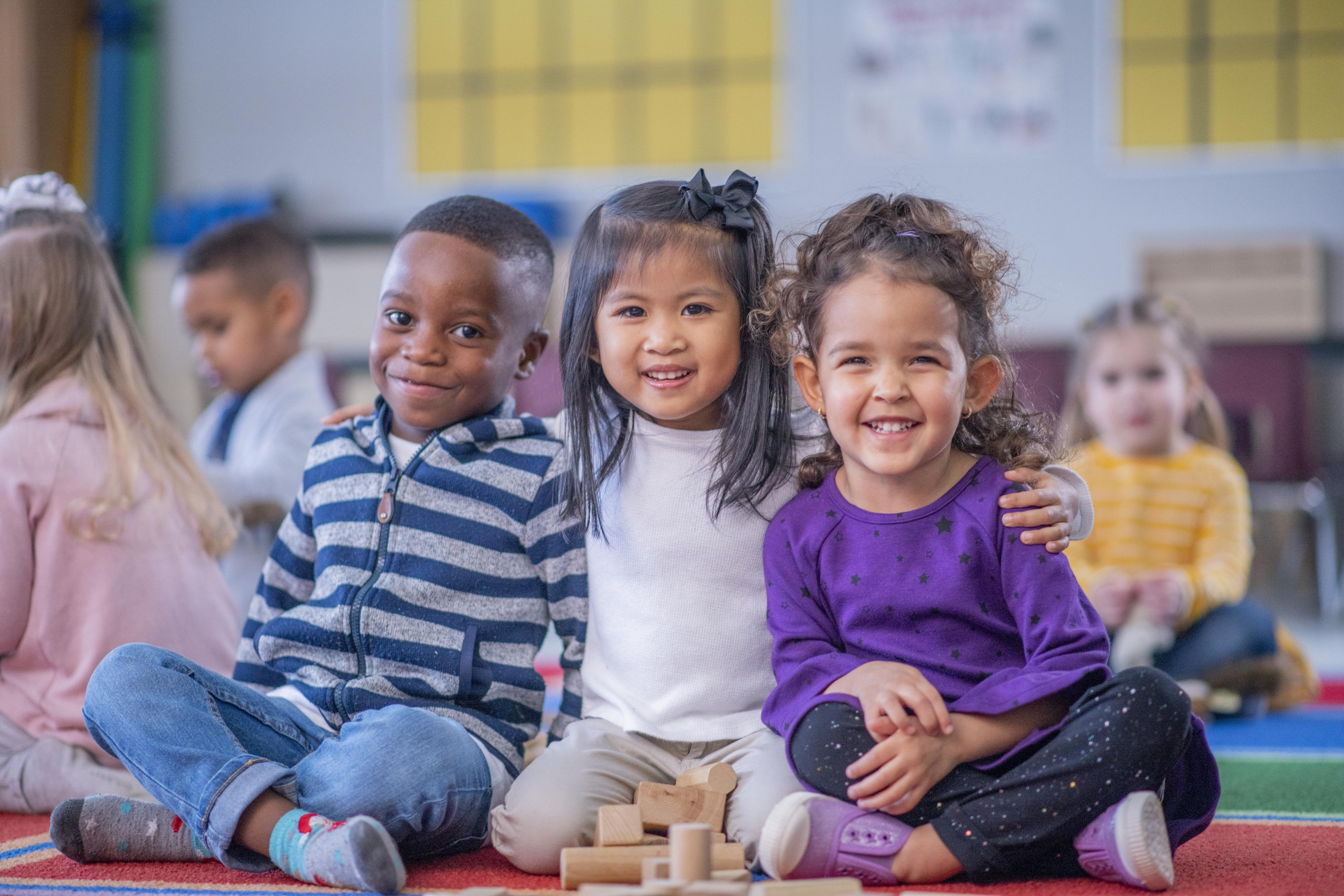 Three children sit together on the floor of a classroom and smile for the camera.