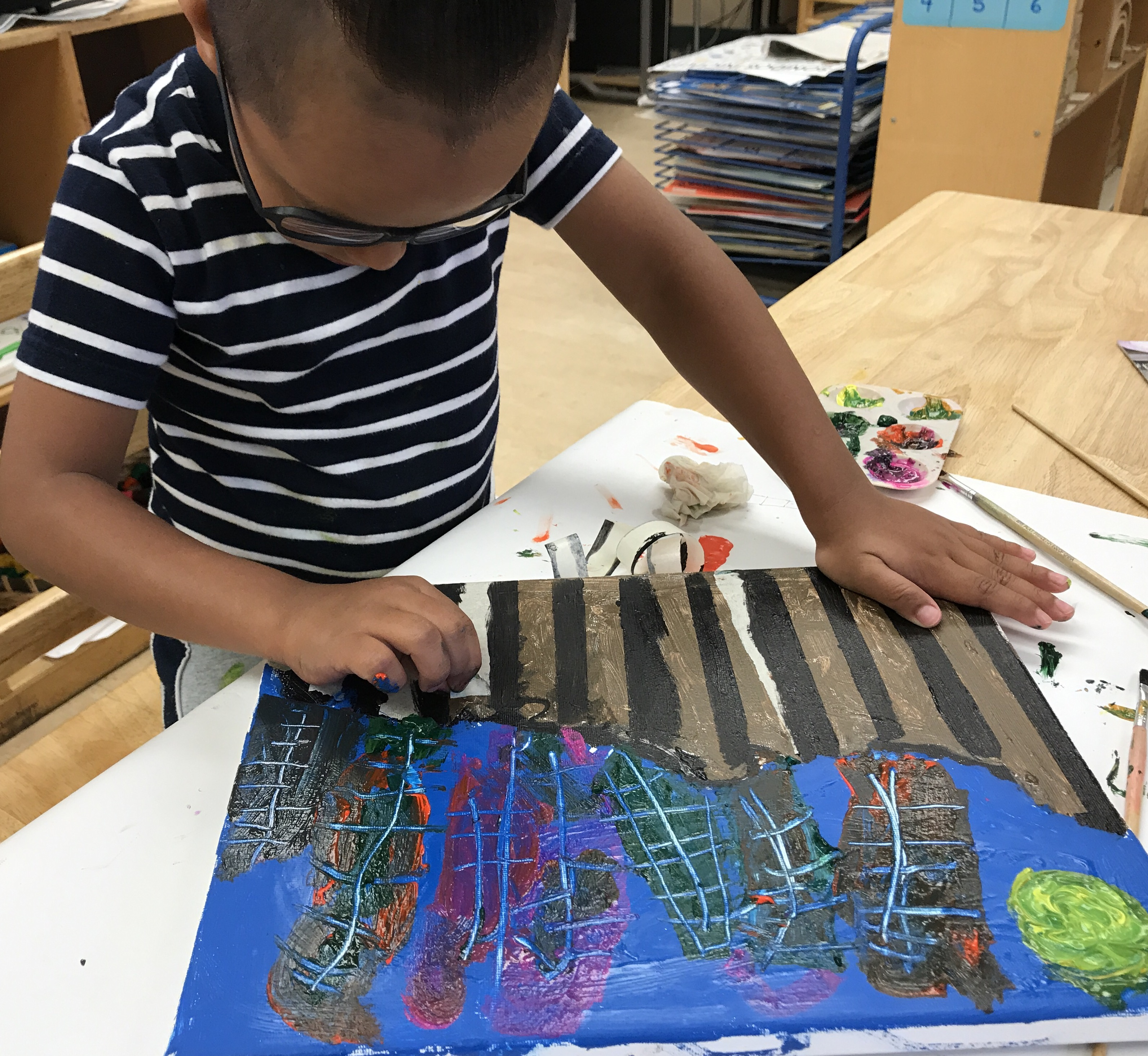 Zahid carefully crafts his picture of the border that separates him from his dad.