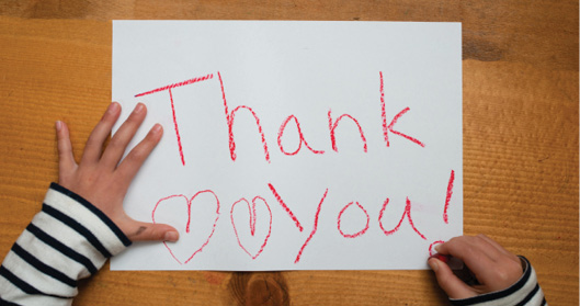 "Two child's hands drawing ""Thank You!"" with two hearts on a white piece of paper with a red crayon"