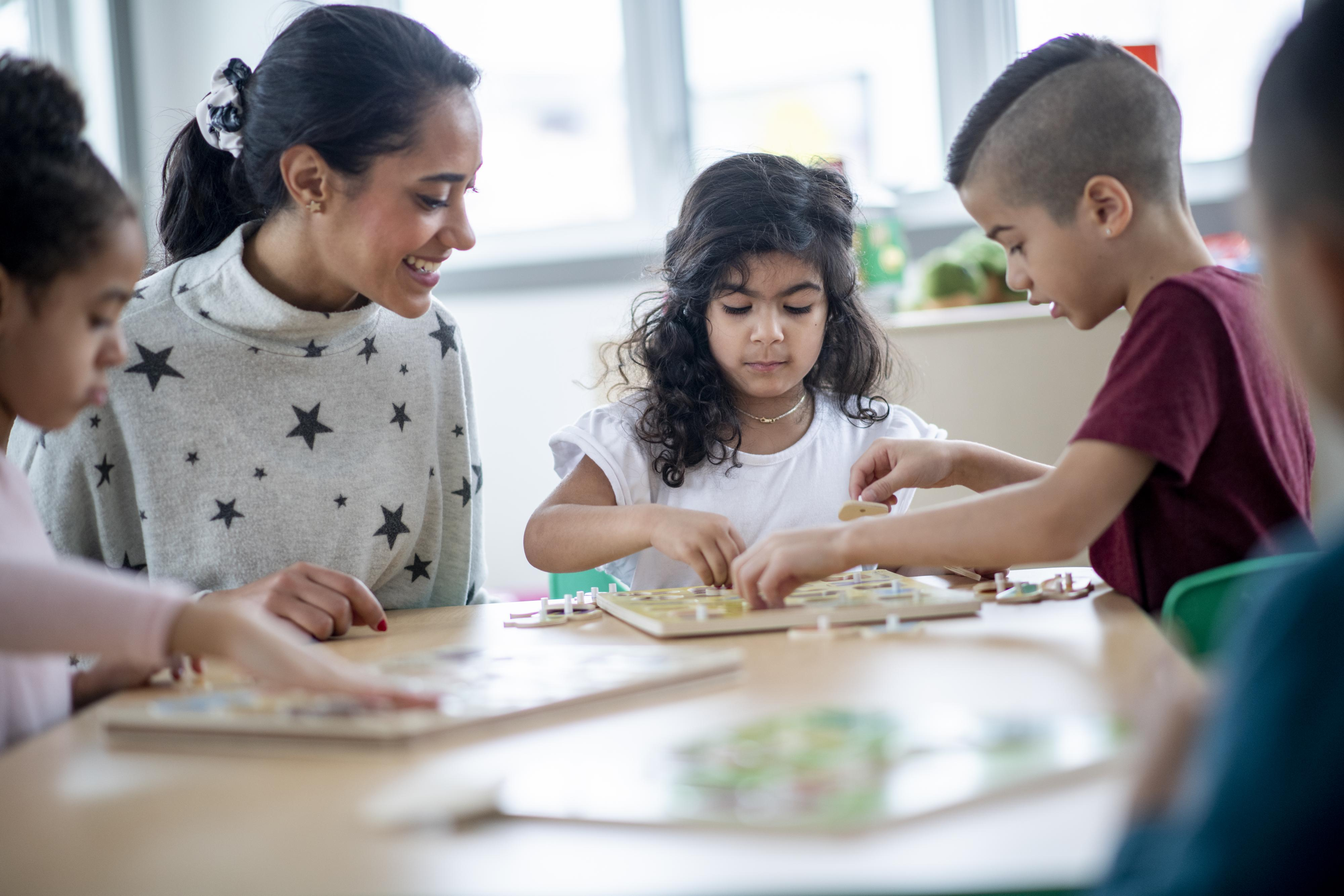 A teacher observes children cooperating with a puzzle.