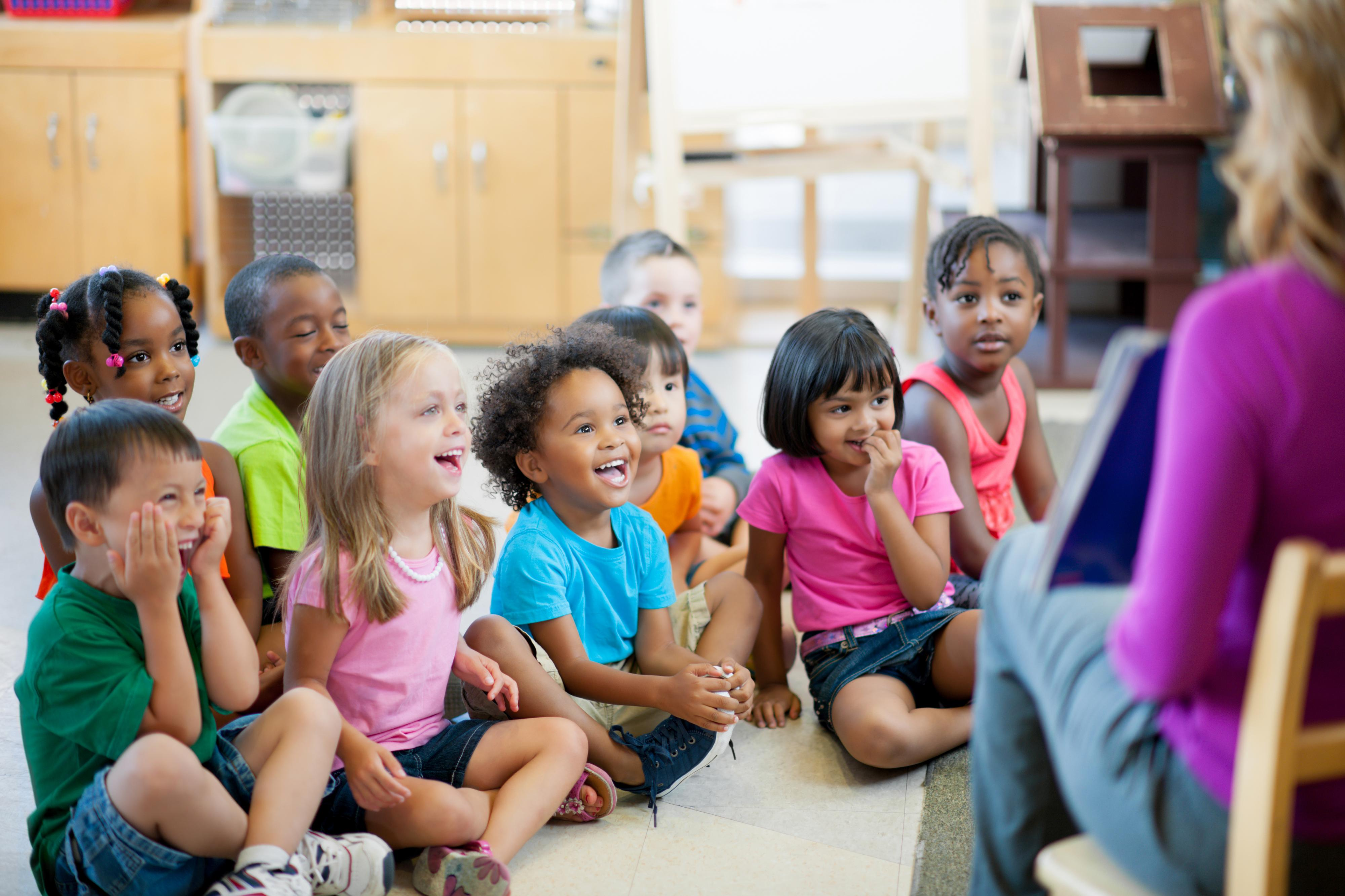 Children interact with their teacher during large-group time.