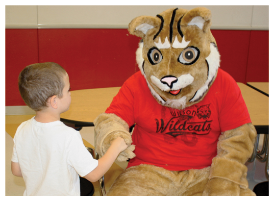One young student shaking hands with a wildcat mascot