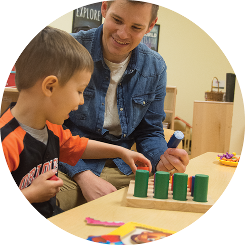 Bryson McCargar playing with cylindrical blocks with one of his students