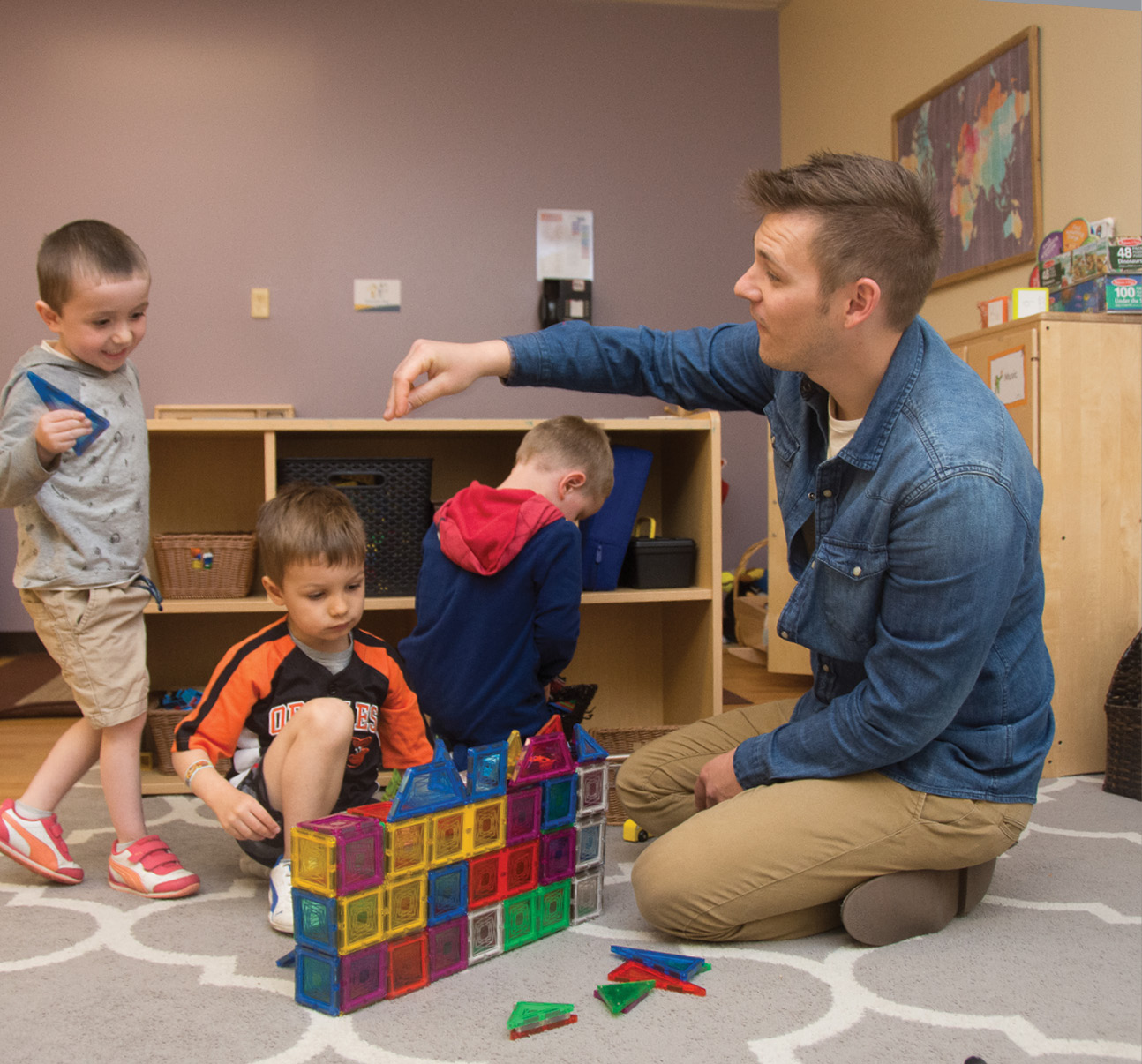 Bryson McCargar playing with magnatiles with three male students on the floor of the classroom
