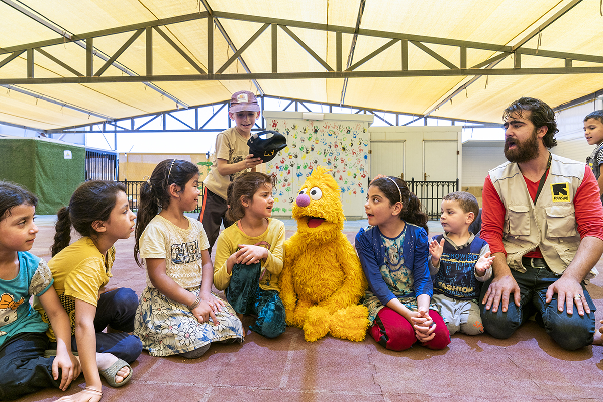 Syrian school children interacting with Muppet