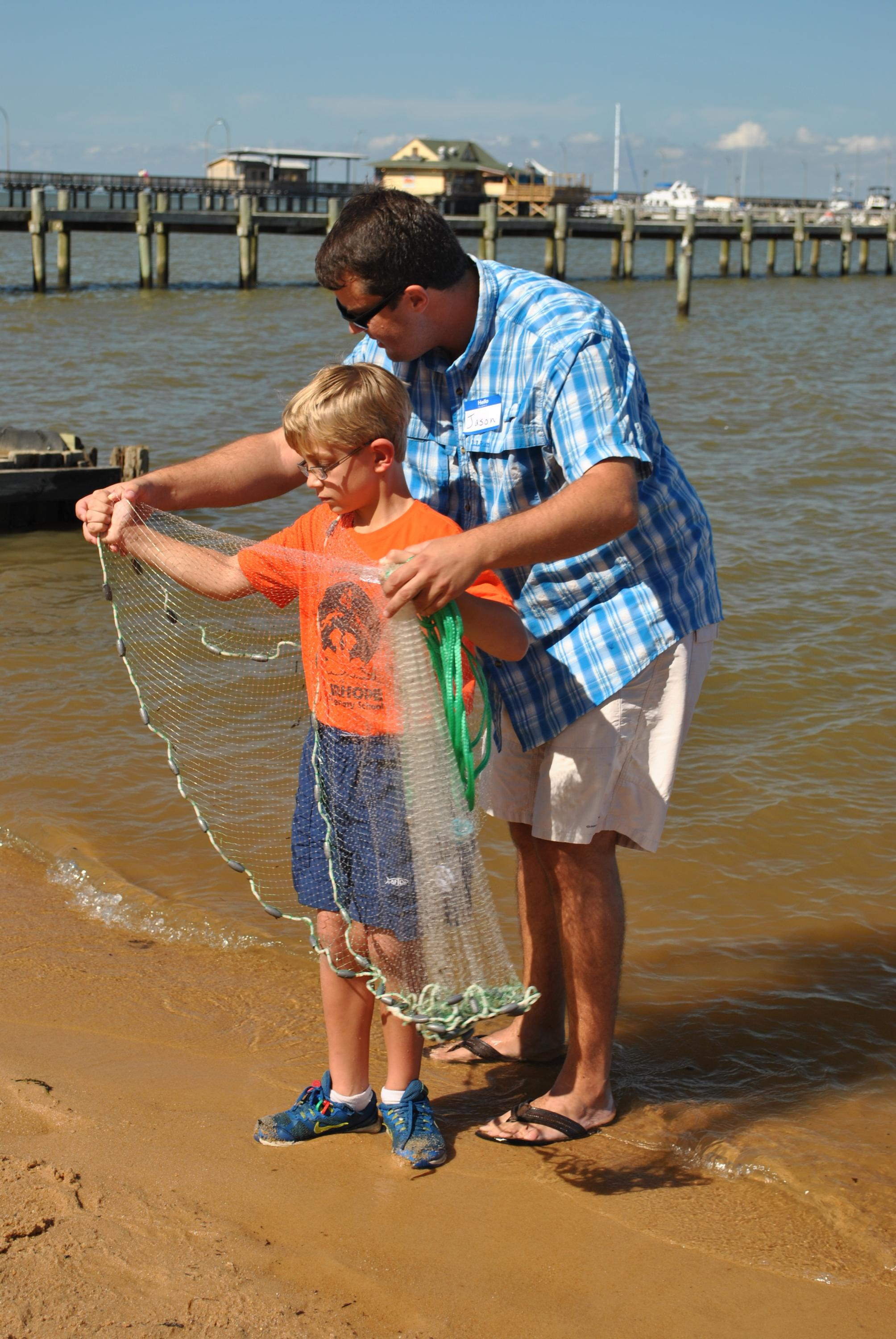 A parent volunteers to teach a child how to throw a cast net.