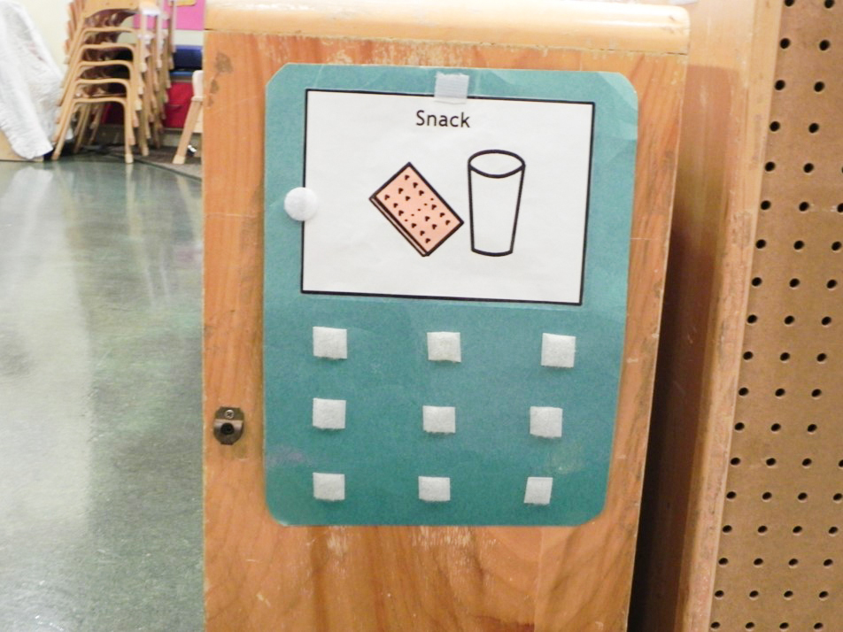 "A velcro poster featuring the graphic ""snack"" with a glass of milk and a graham cracker"