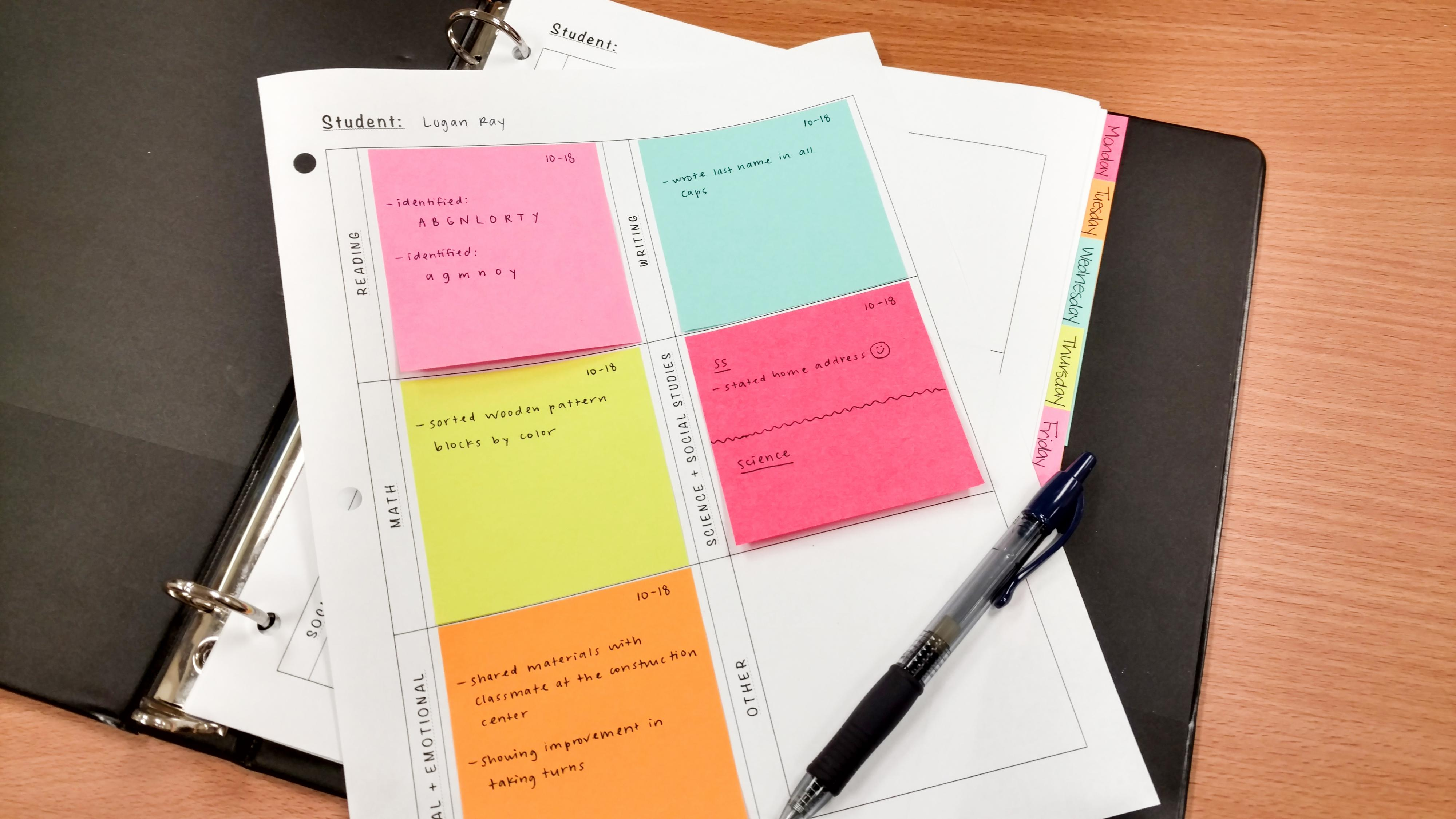 A binder with worksheets featuring written notes on post-it notes