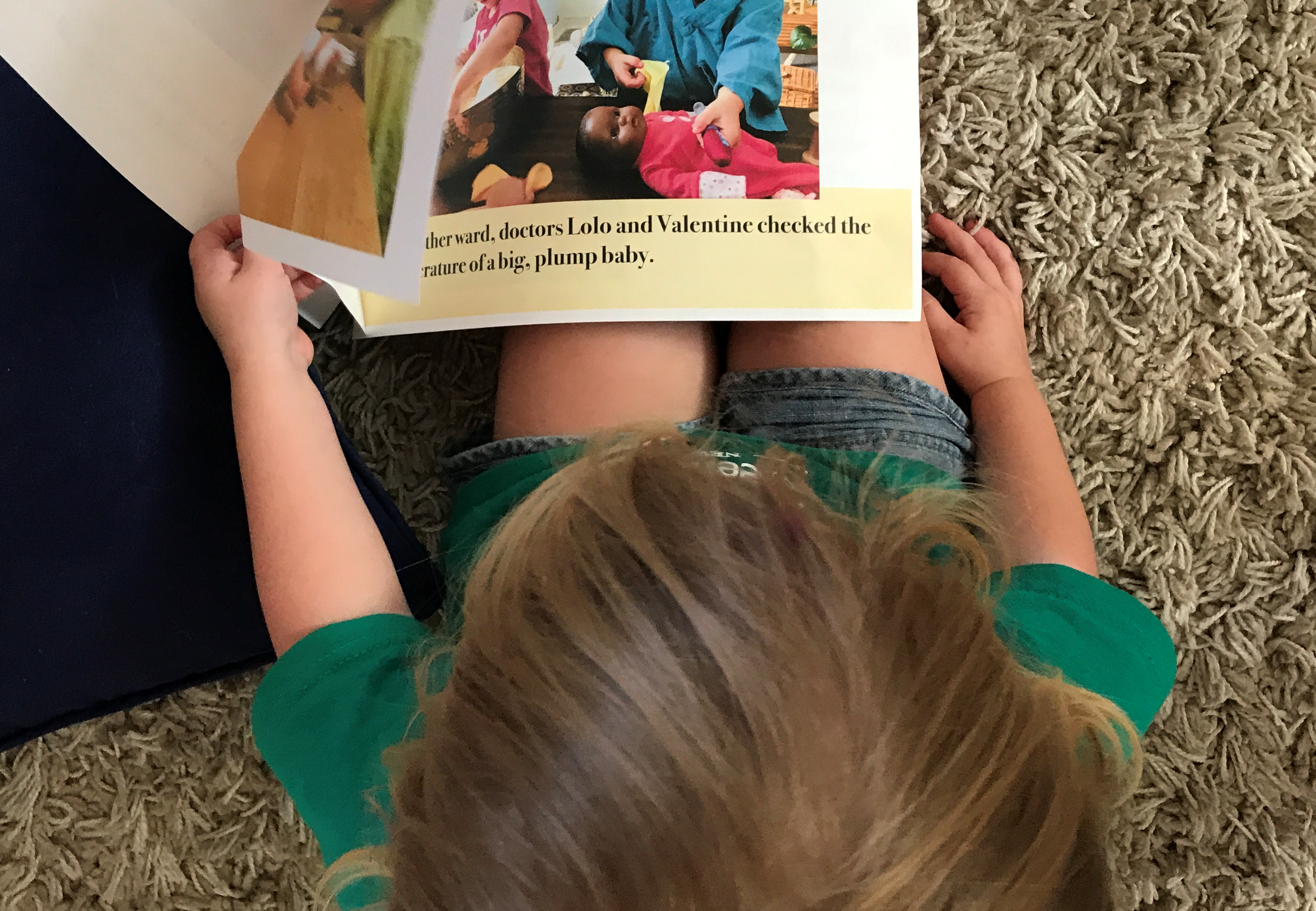 A child looks at the play story booklet about doctors and babydolls.