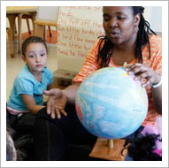 Teacher and student looking at globe