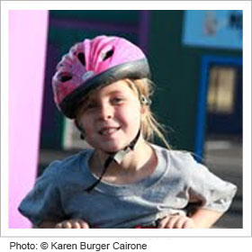 Young girl riding her bike with a helmet