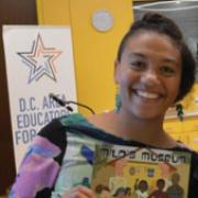 Megan Pamela Ruth Madison holding a children's book and smiling.