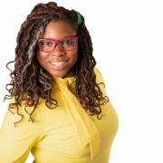 Picture of woman with glasses, braids, in a yellow shirt
