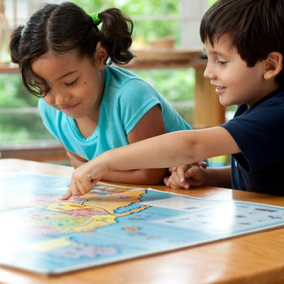 A young boy and girl looking at a map on a table