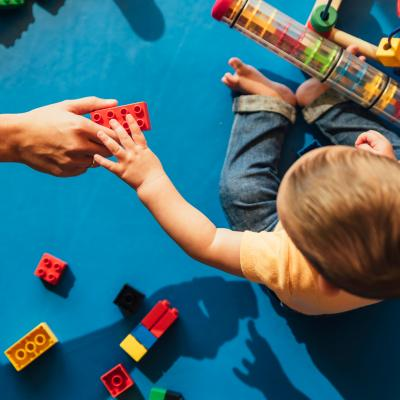 A toddler reaches for a building block from an adult