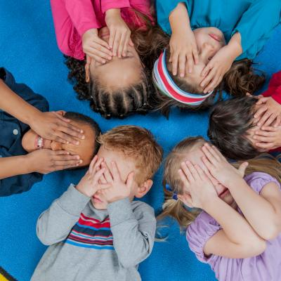 Six diverse young children covering their eyes.