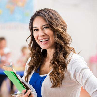 Teacher holding a folder and smiling in classroom