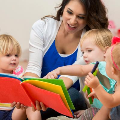 Teacher reading to three preschool students