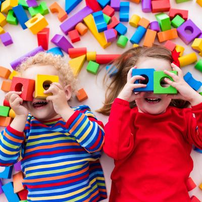 Two toddlers playing in colorful blocks