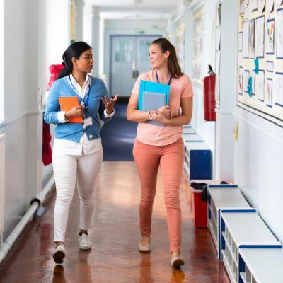 Two women teachers talk in the hallway of a school holding folders.