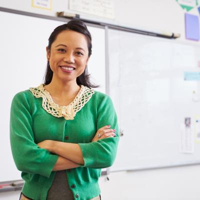 A teacher smiles at the camera in front of a whiteboard.