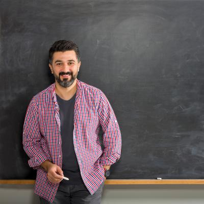 Man with chalk standing in front of chalkboard