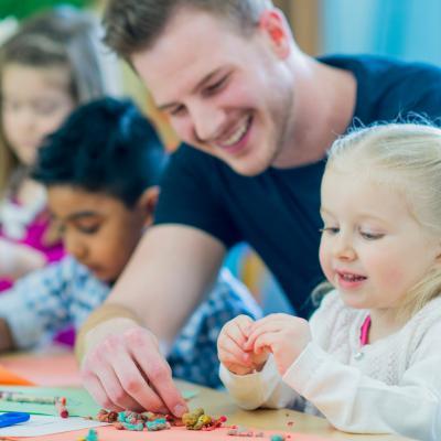 Male teacher helping preschool students