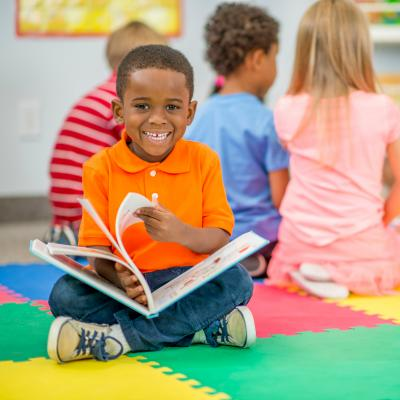 Preschooler reading a book in the classroom.