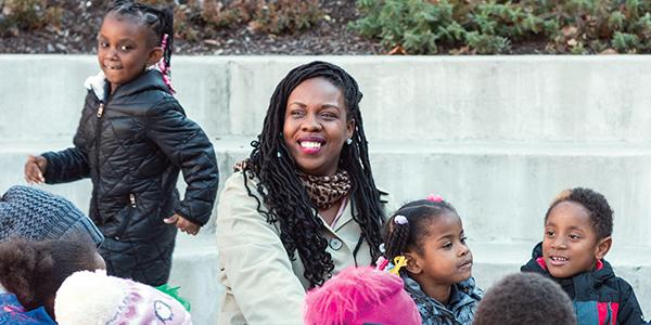 African-American teacher with kindergarten students sitting outside