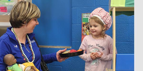Teacher in a classroom with a preschooler