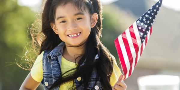 Preschool aged girl holding an american flag