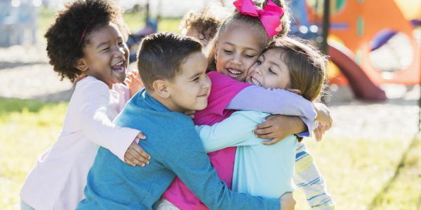 Preschoolers hugging on a playground