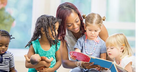 Teacher reads to preschoolers as they look through a book
