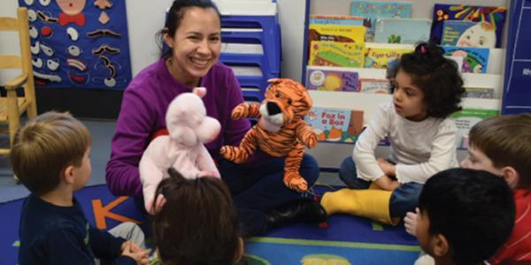 Teacher plays with puppets during group time with toddlers
