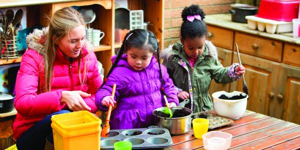Children playing with kitchen utensils outdoors