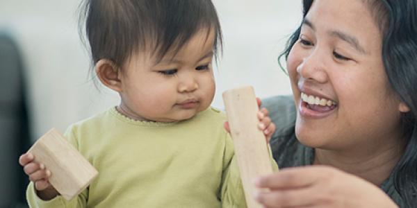 Mother playing with blocks with her young child.