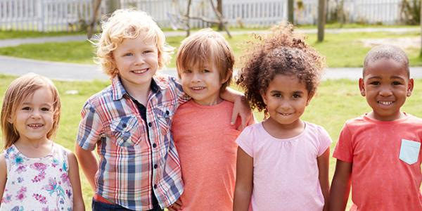 Preschool age children pose for a picture outdoors.