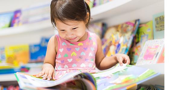 young child reading a picture book