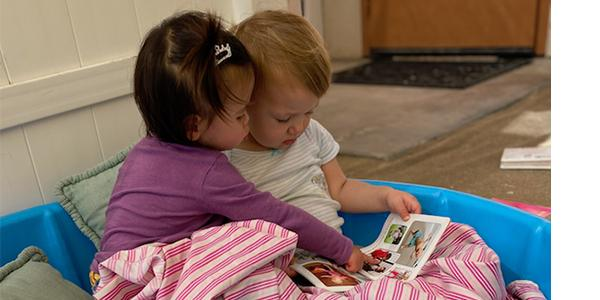 two babies looking at a book