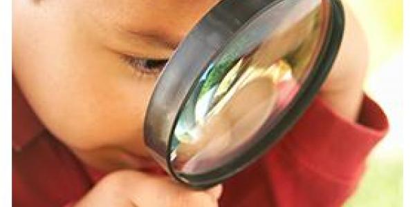 Boy with magnifying glass looking at the grass