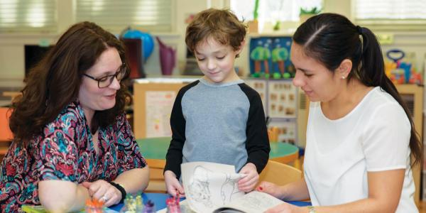 Two teachers looking at book with student