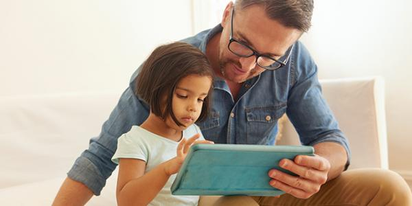 Father and daughter holding a digital tablet
