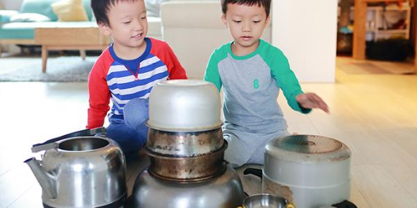 Two boys playing with pots on the kitchen floor