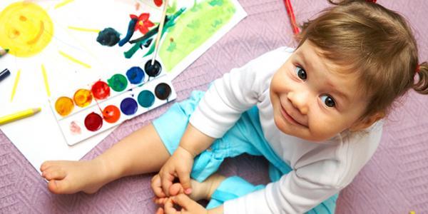 Toddler girl sitting next to art