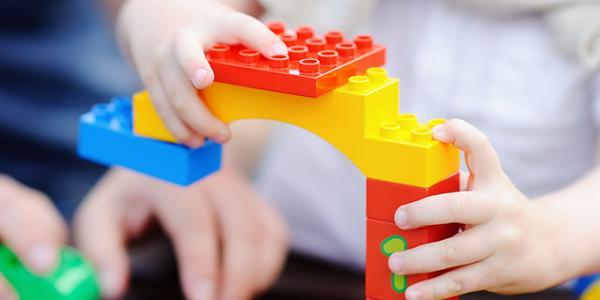 Parent and child's hands building with legos