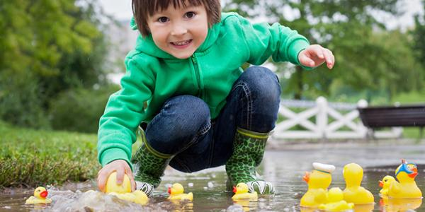 Young child playing with rubber duckies in a puddle outside