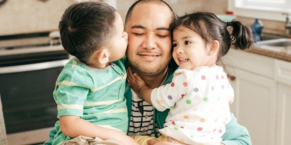 Father hugging toddler son and daughter