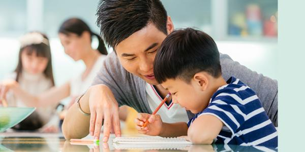 Preschooler and father writing at desk