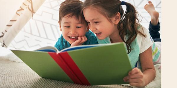 Young boy and girl read a book together