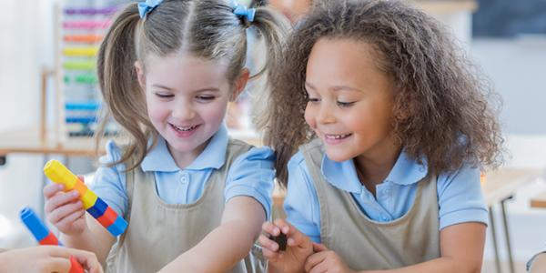 Two preschool girls in a classroom laughing and playing with blocks